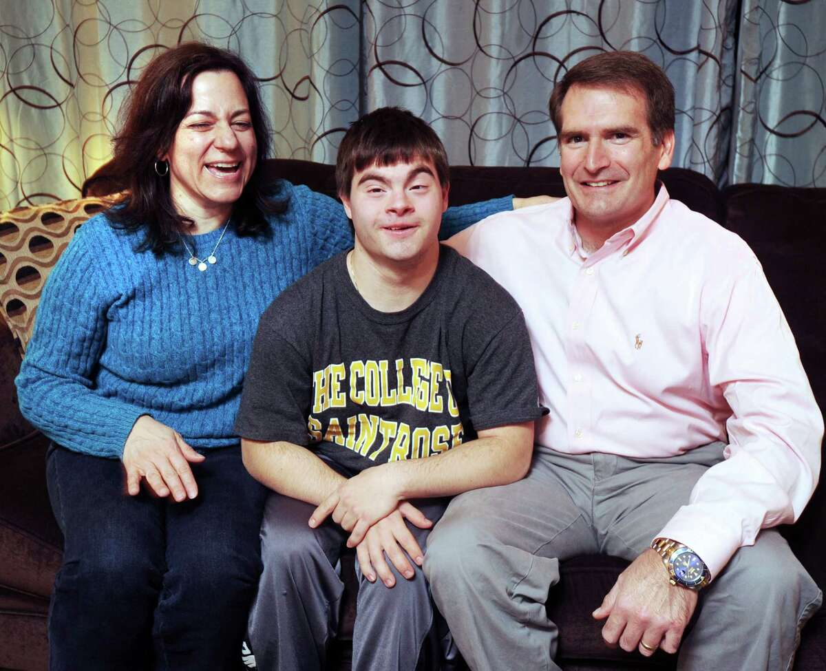 At center, Joe Lupinacci, 19, with his parents, Ida and Rich, in their Stamford home on Tuesday. Lupinacci, a Stamford High School graduate, who has Down's syndrome, is a freshman at the College of Saint Rose in Albany, N.Y.
