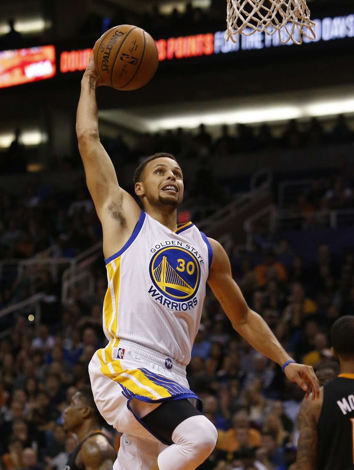 Golden State Warriors guard Stephen Curry (30) scores against the Phoenix Suns in the first quarter during an NBA basketball game, Friday, Nov. 27, 2015, in Phoenix.