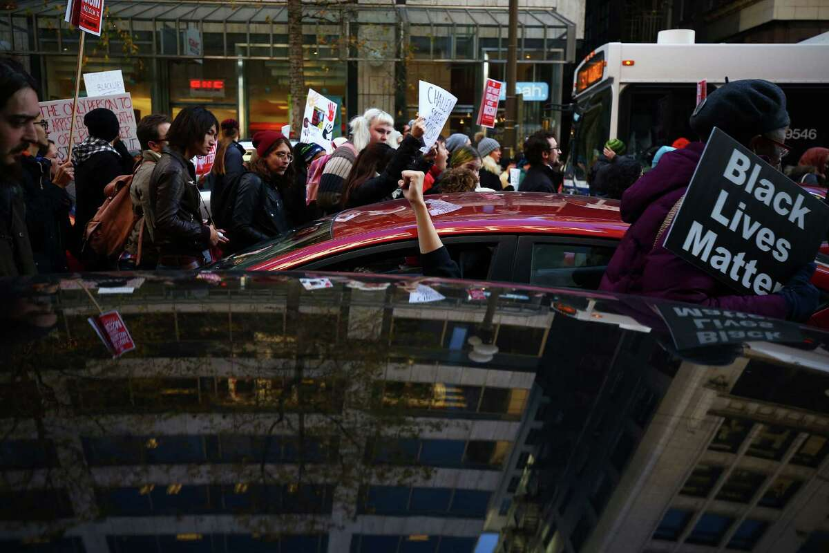 A man in a car raises his fist in solidarity as Black Lives Matters protesters marched through downtown Seattle, including through Westlake Center and Pacific Place mall, Friday, to bring attention to police brutality, civil rights issues, consumerism, Nov. 27, 2015. The march ended at Westlake Park to disrupt the annual tree-lighting ceremony.