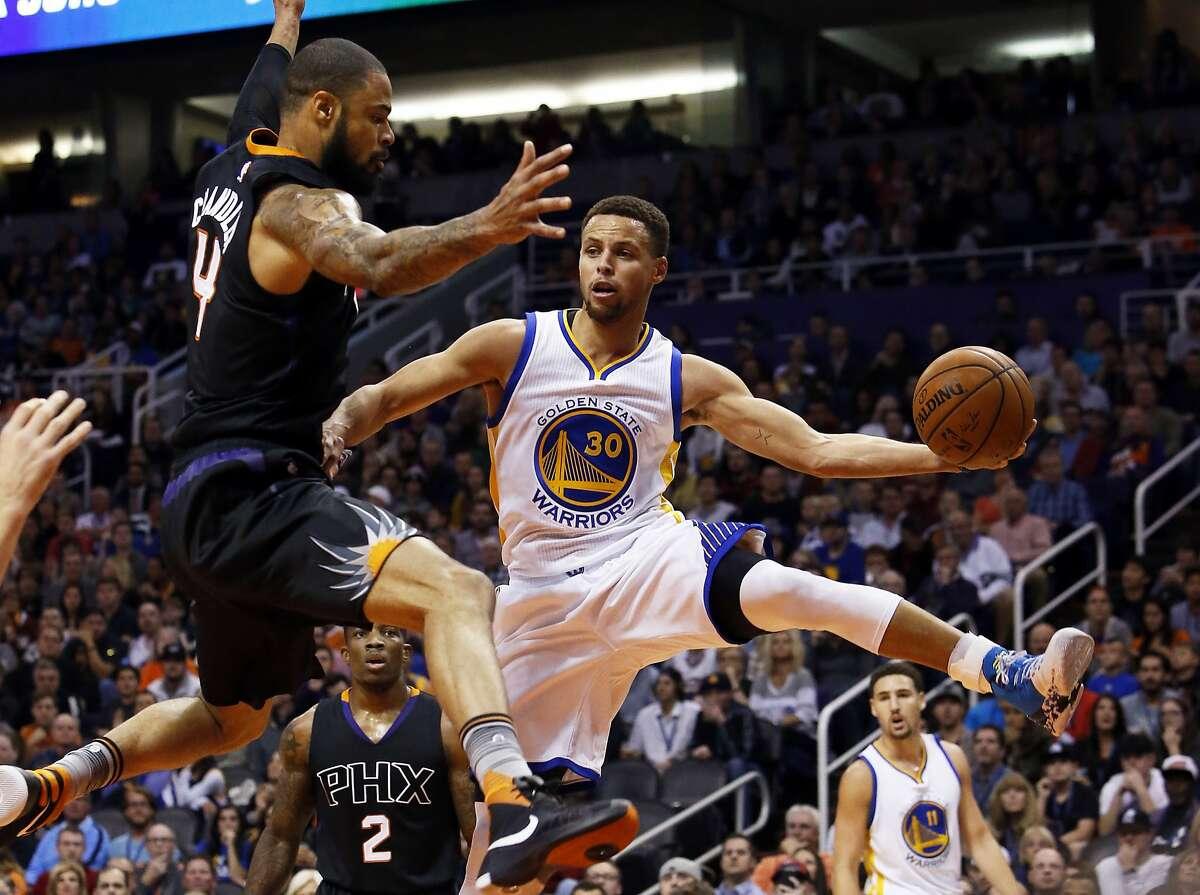 Golden State Warriors guard Stephen Curry (30) drives around Phoenix Suns center Tyson Chandler in the second quarter during an NBA basketball game, Friday, Nov. 27, 2015, in Phoenix. (AP Photo/Rick Scuteri)