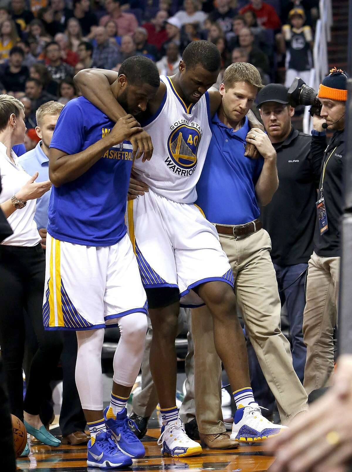 Golden State Warriors forward Harrison Barnes is helped off the court during the third quarter of an NBA basketball game against the Phoenix Suns, Friday, Nov. 27, 2015, in Phoenix.