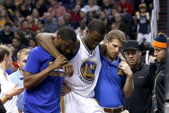 Golden State Warriors forward Harrison Barnes is helped off the court during the third quarter of an NBA basketball game against the Phoenix Suns, Friday, Nov. 27, 2015, in Phoenix. (AP Photo/Rick Scuteri)