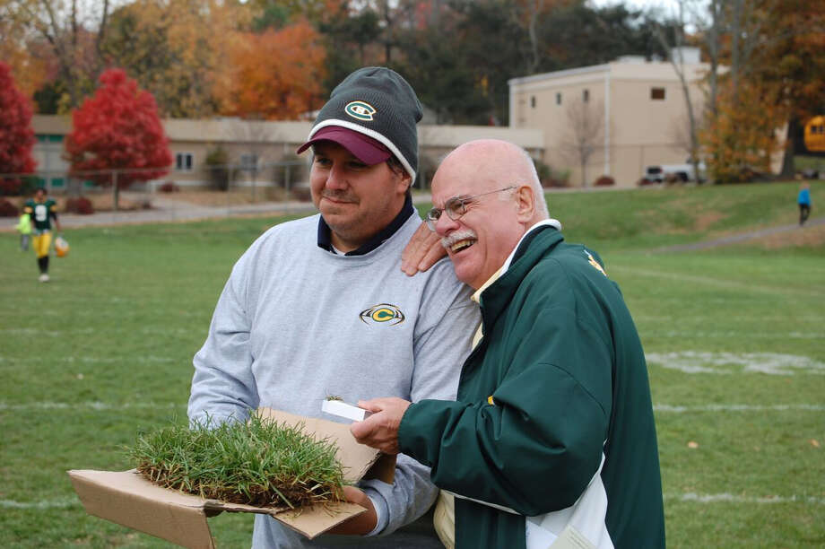 Trinity Catholic alumnus Matt Lacerenza, Class of 1988, and Ernie Bourcier, director of alumni relations, display a piece of the grass sod from Alumni Field on Oct. 31. The Stamford school is switching to a new synthetic playing surface next season. Photo: Contributed Photo / Stamford Advocate Contributed