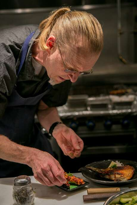 Chef Scott Whitman plates the chicken thigh skewers at Village Sake in Fairfax. Photo: John Storey, Special To The Chronicle