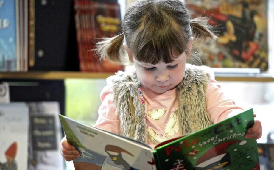 "Lorelai Strano, 2, of Newtown, reads the book ""Pete the Cat Saves Christmas"" with art by James Dean and story by Eric Litwin,   at Byrd's Books in downtown Bethel. Strano was shopping with her mother on Small Business Saturday. November 28, 2015, in Bethel, Conn. Photo: H John Voorhees III, Hearst Connecticut Media / The News-Times"