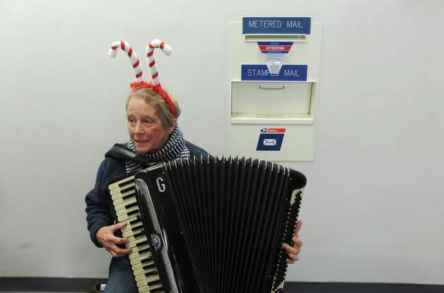Peggy Hart plays with the Squeeze Play Accordion band as volunteers unload boxes of cards at the Glenmont post office for the Christmas Cards to our Troops 2015 on Saturday Nov. 28, 2015 in Glenmont, N.Y. Last year they sent 120,000 from Glenmont NY to all Deployed troops around the world. (Michael P. Farrell/Times Union) Photo: Michael P. Farrell / 00033959A