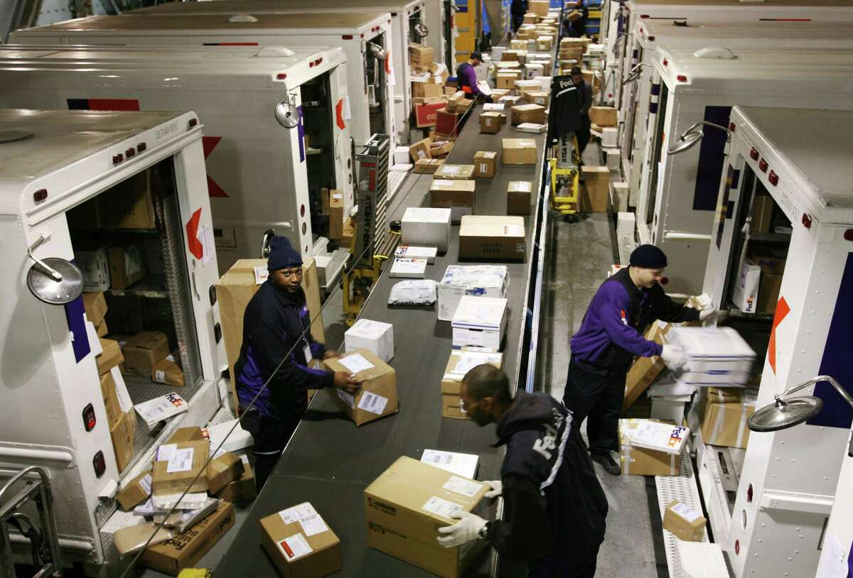 File - FedEx drivers pick packages for their delivery routes from a conveyor belt in a distribution facility on Thursday, Dec. 13, 2007 in New York. (AP Photo/Mark Lennihan)