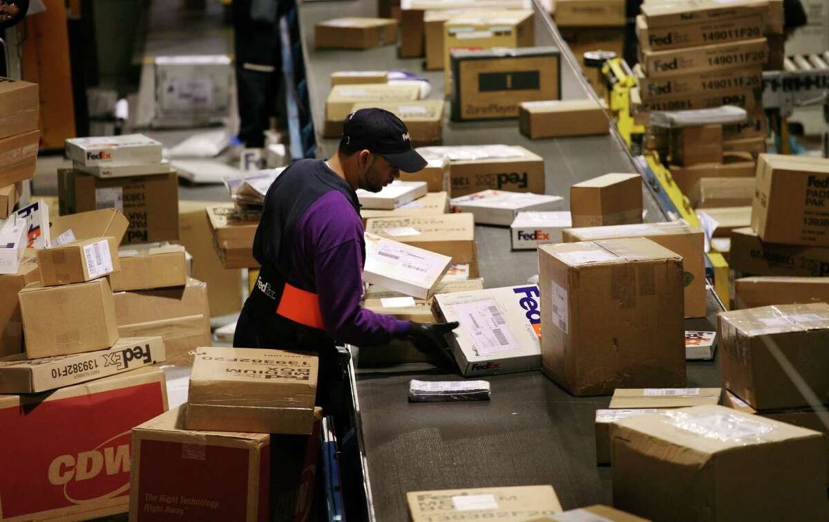 File - A FedEx driver picks packages for his delivery route from a conveyor belt in a distribution facility on Thursday, Dec. 13, 2007 in New York. (AP Photo/Mark Lennihan)