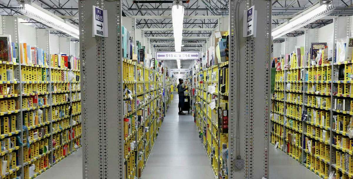 FILE - In this Monday, Dec. 2, 2013, file photo, an Amazon.com employee stocks books at the Amazon.com Fulfillment Center in Phoenix. Holiday sales jobs are now likelier to be in warehouses and trucks than in retail stores. (AP Photo/Ross D. Franklin, File)