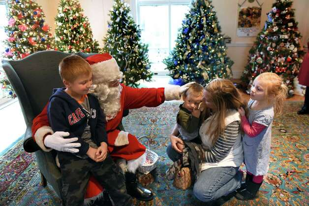 Andon Jerian, 6, of East Schodack, left, sits on Santa's lap while little brother Aren Jerian, 2, holds back with their mother Kate Jerian and sister Ani Jerian, 4, during Home for the Holidays free admission weekend on Saturday, Nov. 28, 2015, at Albany Institute of History and Art in Albany, N.Y. The event continues on Sunday from noon to 4:30 p.m. (Cindy Schultz / Times Union) Photo: Cindy Schultz / 10034425A