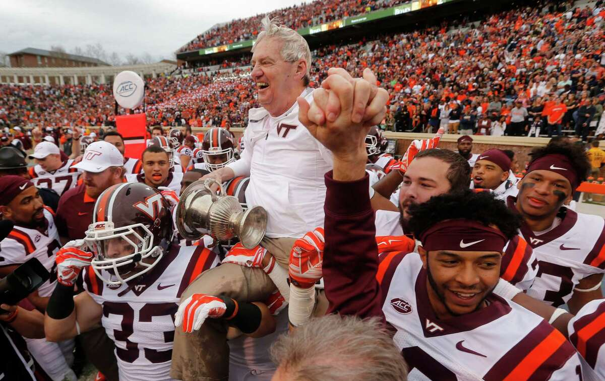 Virginia Tech head coach Frank Beamer is carried off the field while holding the Commonwealth Cup after the Hokies defeated Virginia 23-20 in an NCAA college football game in Charlottesville, Va., Saturday, Nov. 28, 2015. (AP Photo/Steve Helber)