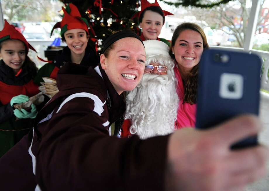Nineteen-year-olds Danielle Clarke, left, and Casey Palmer take a selfie with Santa Saturday, Nov. 28, 2015, on the Sherman Green in Fairfield, Conn. The former Fairfield Warde classmates said they wanted to continue the holiday tradition despite being sophomores in college. Photo: Autumn Driscoll, Hearst Connecticut Media / Connecticut Post