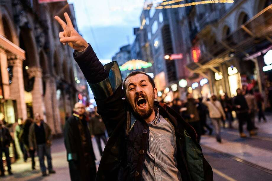 A lawyer flashes the victory sign during clashes between protesters and Turkish riot police on Istiklal avenue in Istanbul after a top Kurdish lawyer was killed in Diyarbakir on November 28, 2015. A leading Kurdish lawyer was shot dead in southeast Turkey after unknown attackers opened fire on a gathering in the mainly Kurdish province of Diyarbakir, triggering a shootout with police, local officials and witnesses said. The unknown assailants shot at Tahir Elci, head of the bar association in Diyarbakir, and 40 other activists as they were giving a press statement near a mosque in the city's Sur district, according to witnesses. Photo: Ozan Kose, AFP / Getty Images