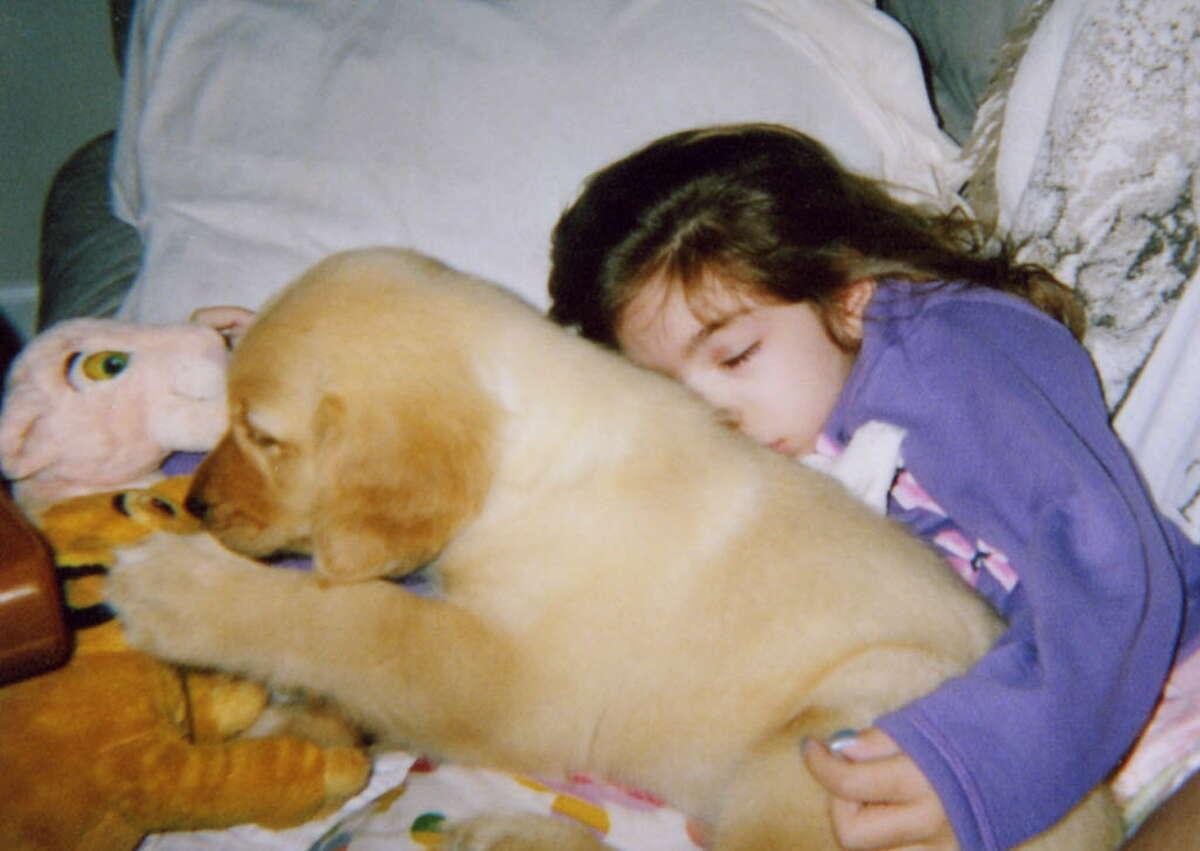 Rachel Rodino, 7, sleeps with her golden retriever puppy Sadie in this?undate photo of the Guilderland girl. (Courtesy / Renee Bernard)