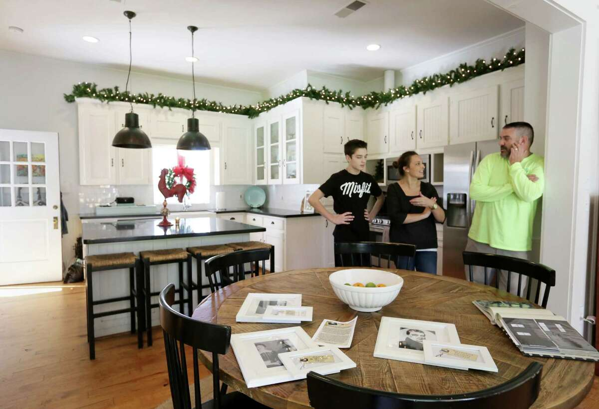 Tommy Hauser, right, his wife Julie and their son Will, 14, talk in their kitchen.