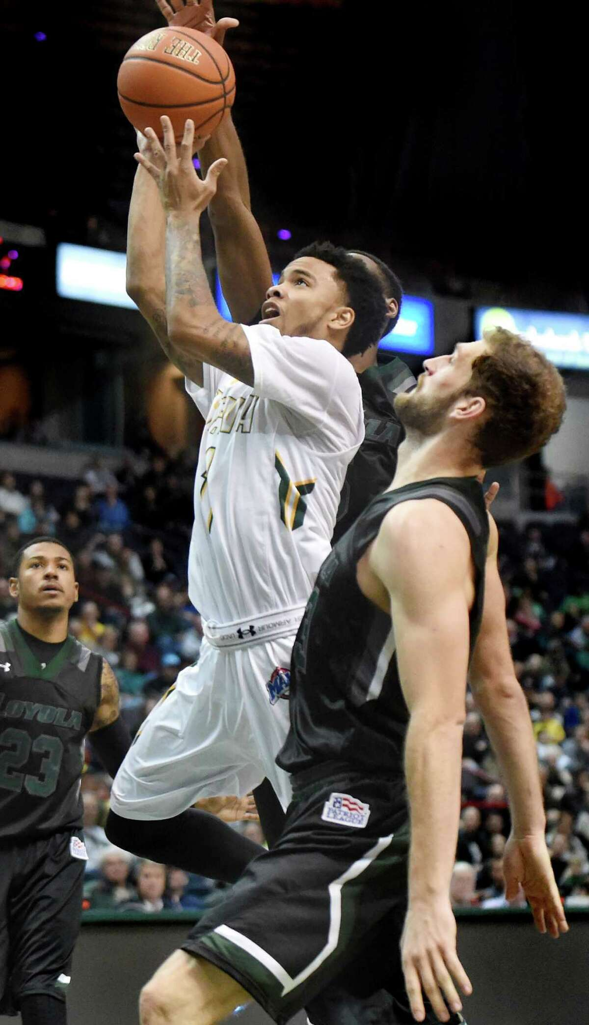 Siena's Marquis Wright, center, breaks for the hoop through Loyola's defense during their basketball game on Saturday, Nov. 28, 2015, at Times Union Center in Albany, N.Y. (Cindy Schultz / Times Union)
