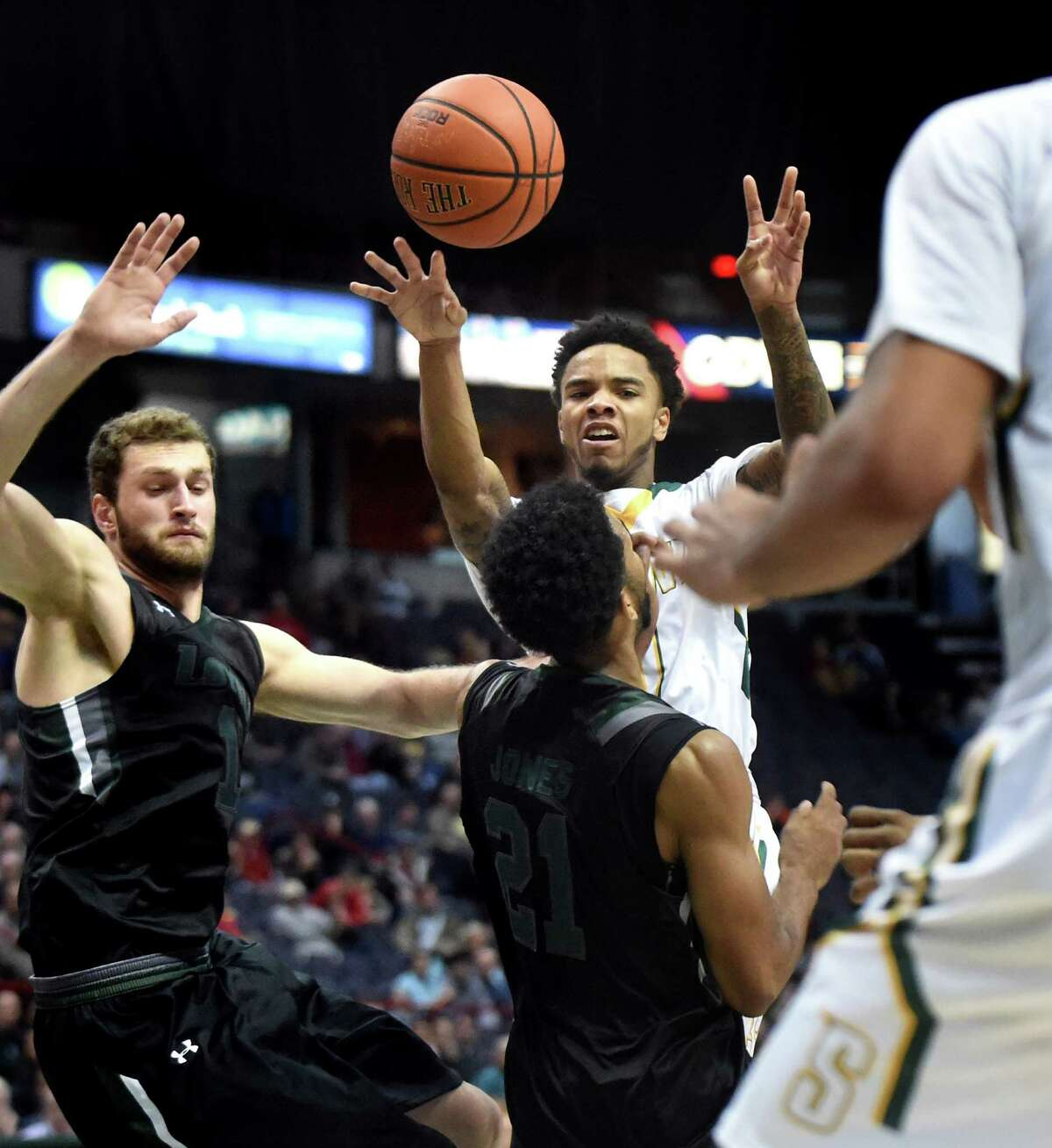 Siena's Marquis Wright, center, passes the ball over Loyola's defense during their basketball game on Saturday, Nov. 28, 2015, at Times Union Center in Albany, N.Y. (Cindy Schultz / Times Union)