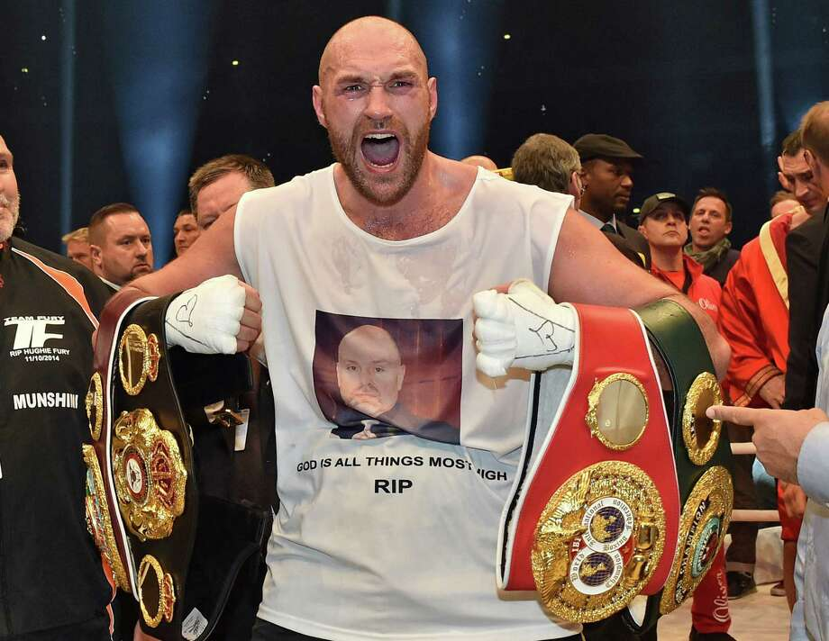 Britain's new world champion Tyson Fury celebrates with the WBA, IBF, WBO and  IBO belts after winning the world heavyweight title fight against Ukraine's Wladimir Klitschko in the Esprit Arena in Duesseldorf, western Germany, Sunday, Nov. 29, 2015. (AP Photo/Martin Meissner) Photo: Martin Meissner, Associated Press / AP