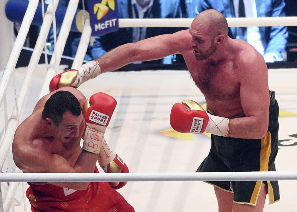 Ukraine's Wladimir Klitschko, left, and Britain's Tyson Fury exchange blows in a world heavyweight title fight for Klitschko's WBA, IBF, WBO and IBO belts in the Esprit Arena in Duesseldorf, western Germany, Saturday, Nov. 28, 2015. (AP Photo/Sebastian Konopka)