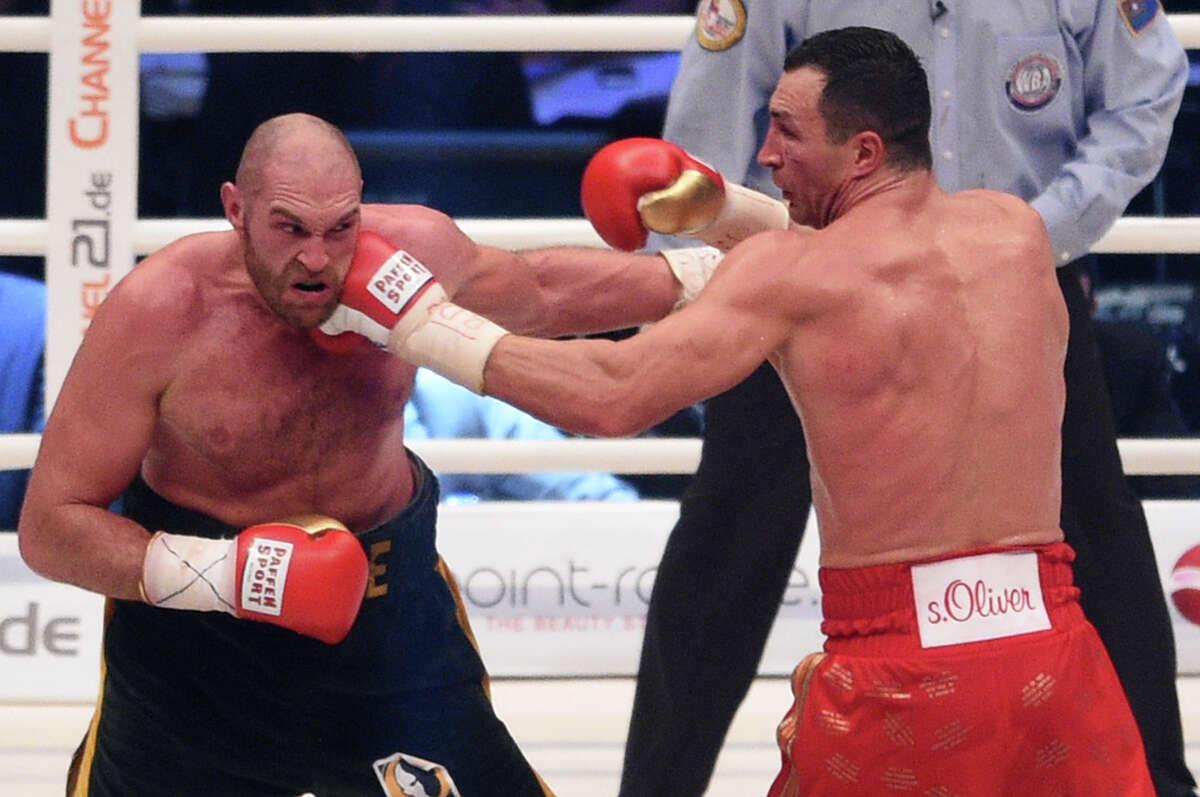 Ukraine's Wladimir Klitschko, right, punches Britain's Tyson Fury in a world heavyweight title fight for Klitschko's WBA, IBF, WBO and IBO belts in the Esprit Arena in Duesseldorf, western Germany, Saturday, Nov. 28, 2015. Fury won the bout. (AP Photo/Sebastian Konopka)