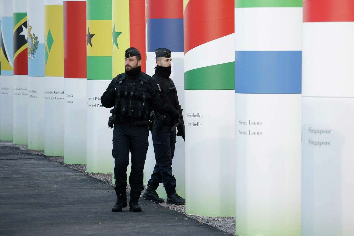 Policemen patrol outside the main entrance of the United Nations Climate Change Conference in Le Bourget, outside Paris, Saturday, Nov. 28, 2015. The site of Paris-Le Bourget will officially become a United Nations territory for the COP 21 conference with more than 100 heads of state and scheduled to start on Nov. 30. (AP Photo/Laurent Cipriani) ORG XMIT: CIP113
