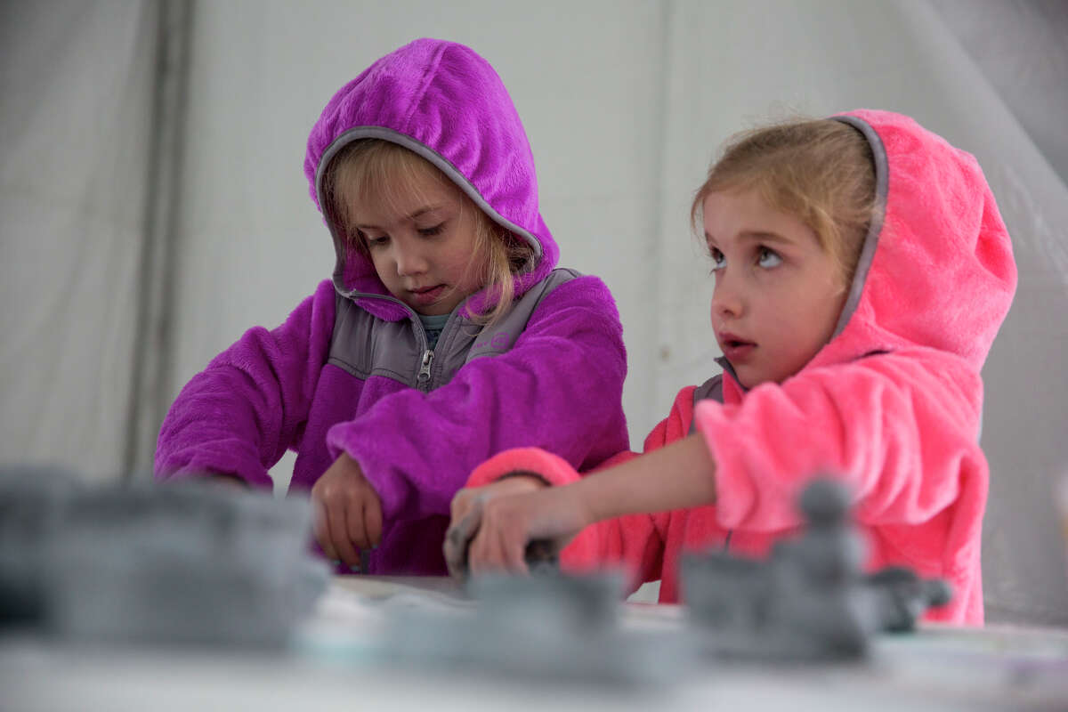 Abby Durkin, left, and her twin sister Emma Durkin, both 5, make clay pots in the Kid's Village area during the Wimberley Alive event in Wimberley, Texas on November 28, 2015. The event is a fundraiser for victims of the Memorial Day floods along the Blanco River. The booth was hosted by Laura Green of the Art Vine Studio. Green was also the chairman of the Kid's Village.