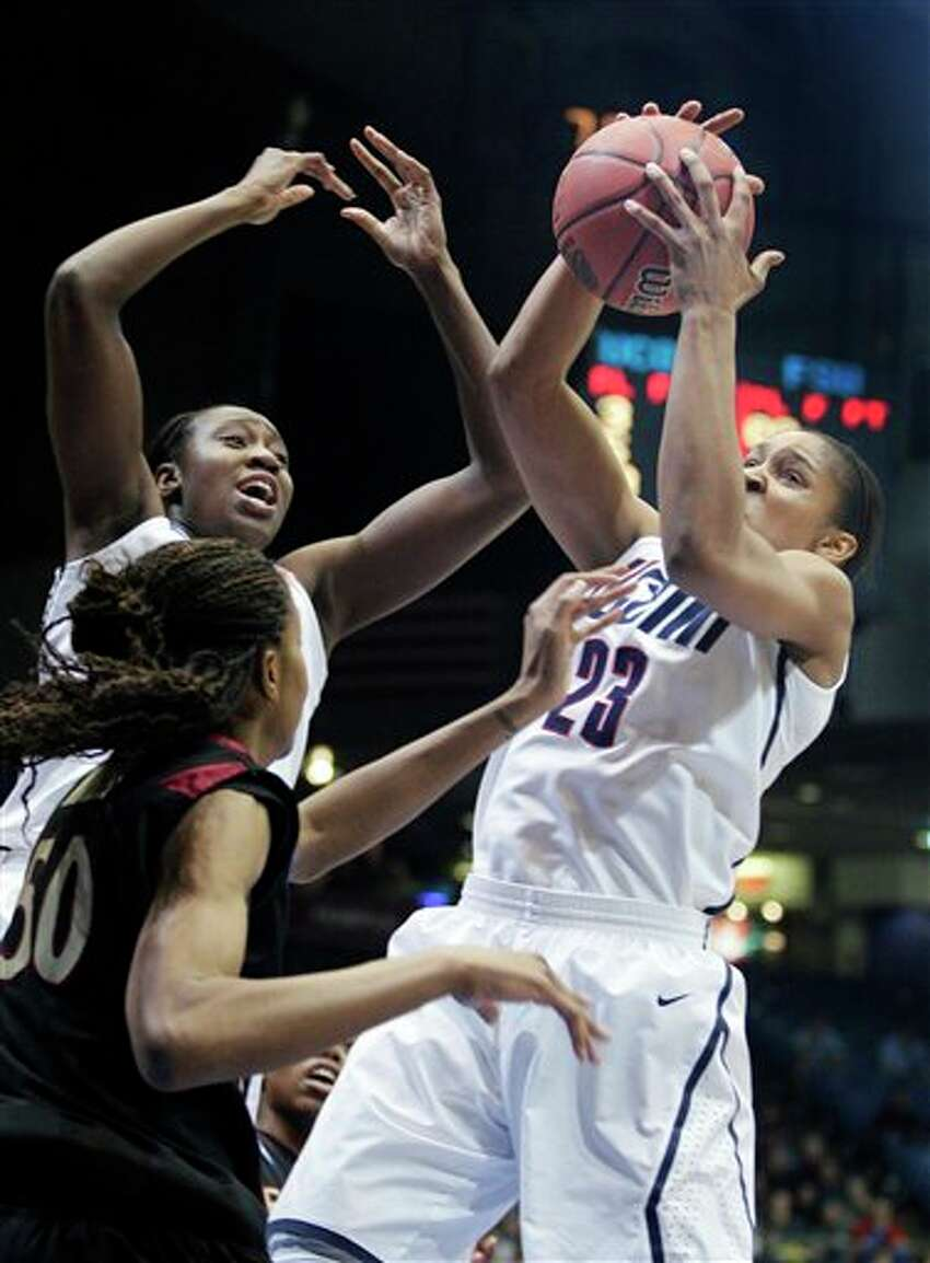 Connecticut's Maya Moore (23) grabs a rebound in front of Florida State's Chasity Clayton in the first half of the NCAA Dayton Regional final college basketball game Tuesday, March 30, 2010, in Dayton, Ohio. (AP Photo/Skip Peterson)