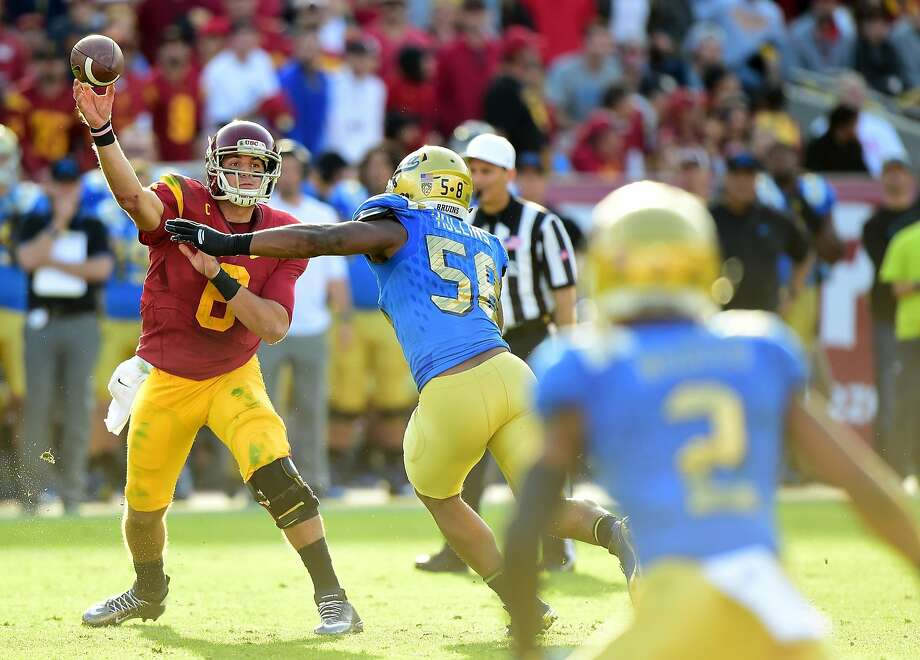 USC's Cody Kessler launches a pass in the face of UCLA pass rusher Deon Hollins on Saturday. Photo: Harry How, Getty Images