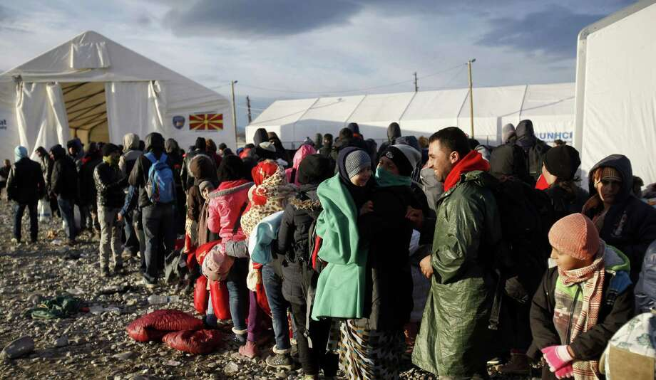 Refugees queue before entering in a transit center for refugees near southern Macedonian town of Gevgelija, after crossing the border from Greece, Saturday, Nov. 28, 2015. Macedonia has started to erect a fence on its southern border with neighboring Greece in order to prevent illegal crossings and to channel the flow of migrants through the official checkpoint, where only migrants from the war-affected zones will be allowed to enter. (AP Photo/Boris Grdanoski) Photo: Boris Grdanoski, STR / AP