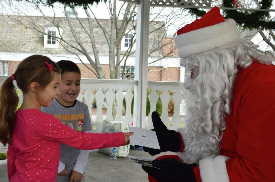 Nina Auriemna, 4, of Fairfield was thrilled with the chance to personally hand Santa Claus a card she'd written Saturday at Sherman Green, while friend Michael Bernardi, 5, of Fairfield, looks on. Photo: Jarret Liotta / For Hearst Connecticut Media / Fairfield Citizen