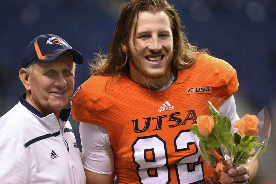 UTSA senior tight end David Morgan II carries flowers as he stands with coach Larry Coker before the team's game against Middle Tennessee State in college football action in the Alamodome on Nov. 28, 2015. Photo: Billy Calzada /San Antonio Express-News / San Antonio Express-News