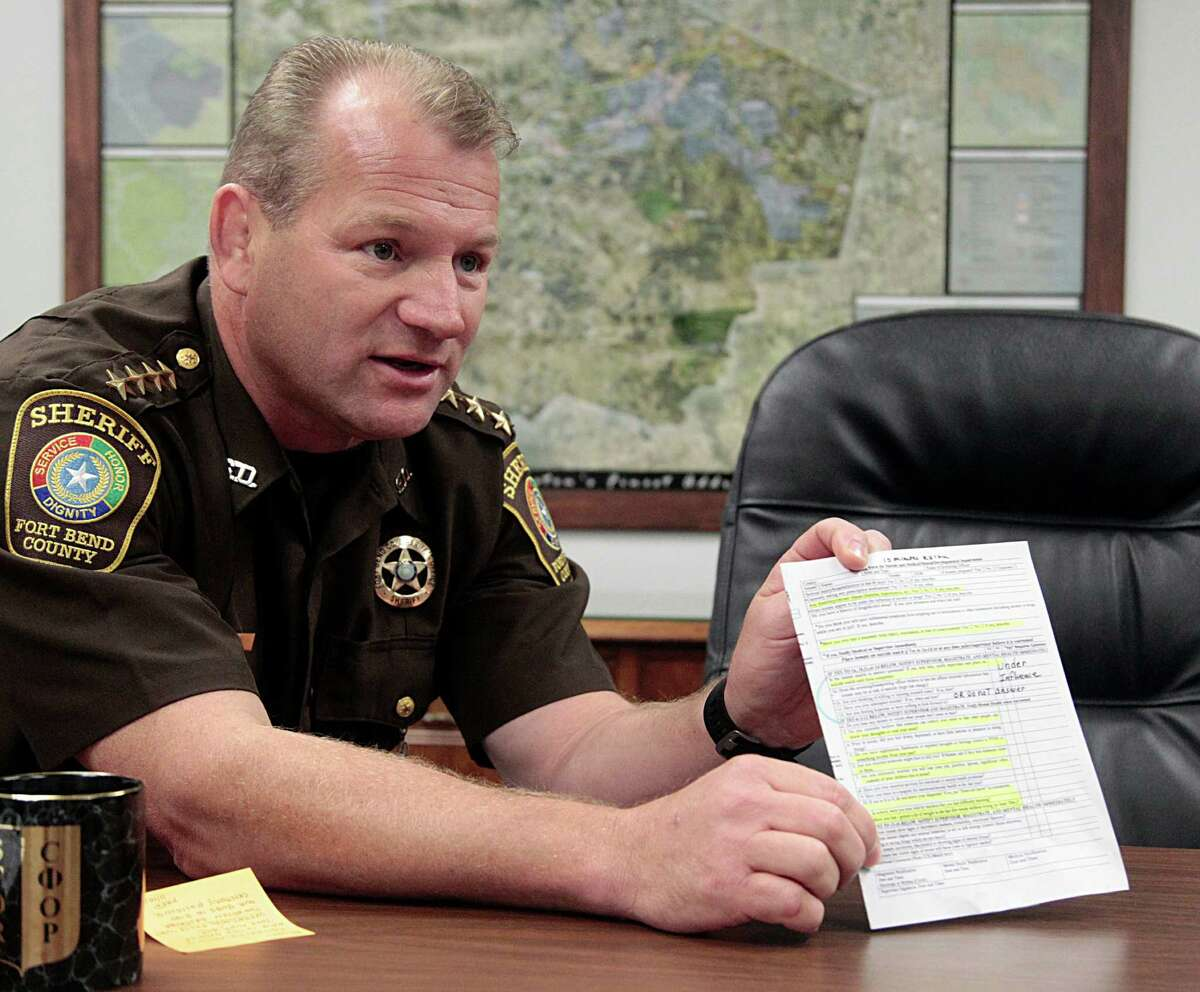 Fort Bend County Sheriff Troy Nehls holds a Screening Form for Suicide and Medical and Mental Impairments during an interview on recent suicides in the county's jail Monday, Nov. 16, 2015, in Richmond.