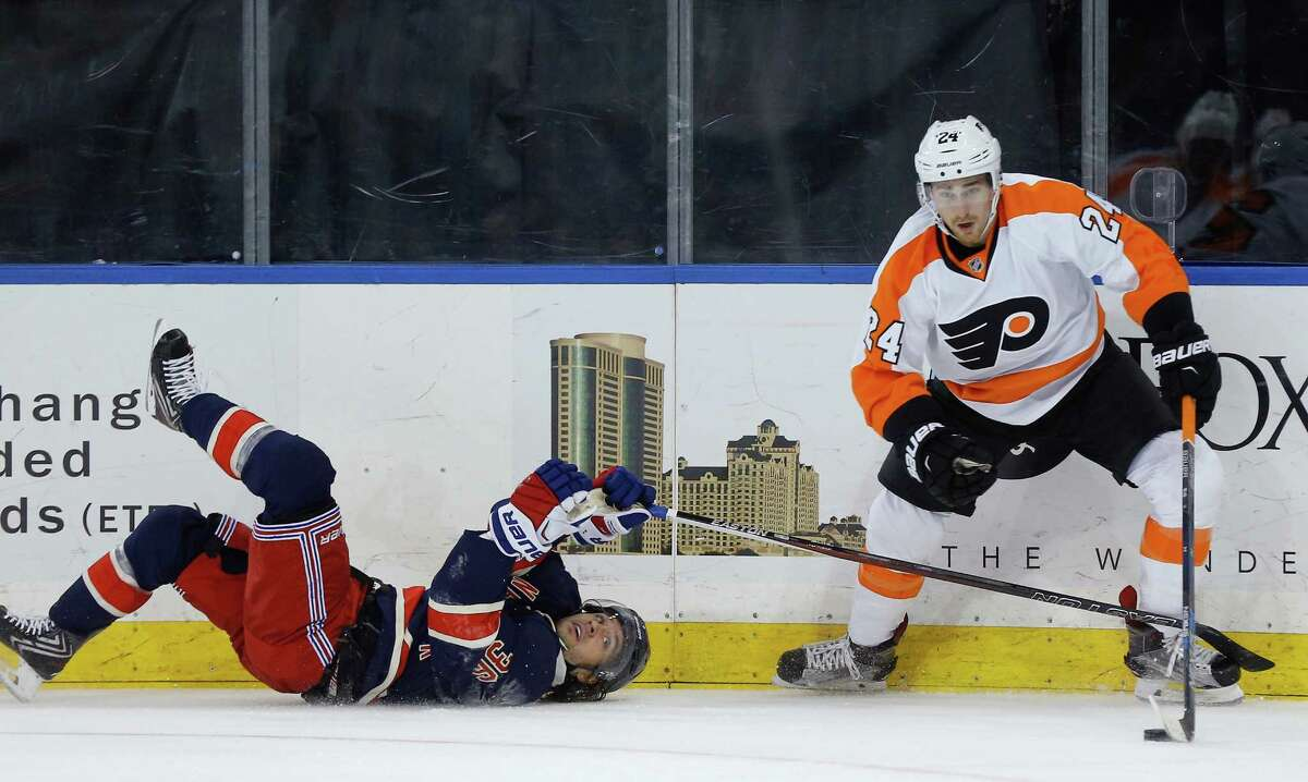 New York Rangers right wing Mats Zuccarello (36) tries to pick the puck from Philadelphia Flyers right wing Matt Read (24) after falling to the ice during the first period of an NHL hockey game, Saturday, Nov. 28, 2015, in New York. (AP Photo/Julie Jacobson) ORG XMIT: NYJJ103