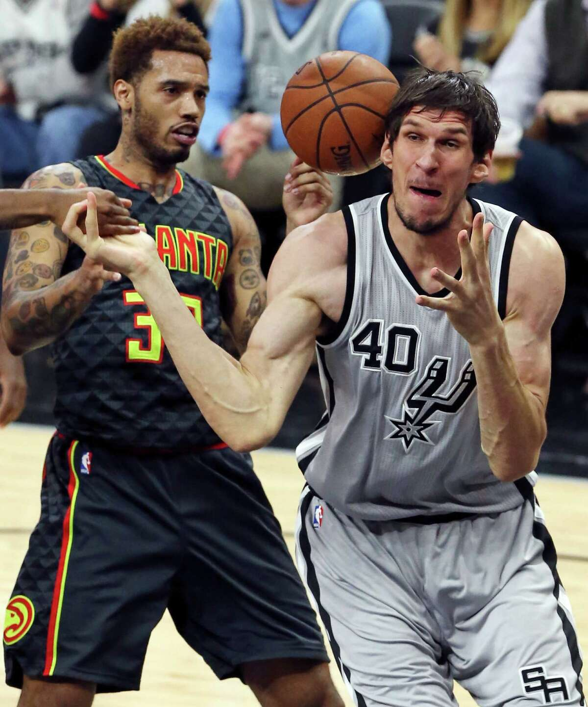 Atlanta Hawks' Mike Scott and San Antonio Spurs' Boban Marjanovic grab for a loose ball during second half action Saturday Nov. 28, 2015 at the AT&T Center. The Spurs won 108-88.