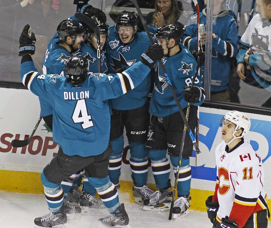 Sharks' center Tomas Hertl (second from right) celebrates with teammates after scoring against the Calgary Flames during the first period in San Jose. The Flames' Mikael Backlund is at right. \ Photo: George Nikitin, Associated Press