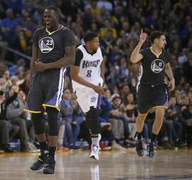 Golden State Warriors forward Draymond Green (23) reacts after guard Klay Thompson, right, hit a three-point shot against Sacramento Kings forward Rudy Gay, center, during the first half of an NBA basketball game Saturday, Nov. 28, 2015, in Oakland, Calif. (AP Photo/Tony Avelar)