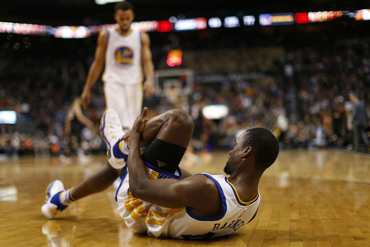 Harrison Barnes #40 of the Golden State Warriors holds his injured leg on the court during the second half of the NBA game against the Phoenix Suns at Talking Stick Resort Arena on November 27, 2015 in Phoenix, Arizona. The Warriors defeated the Suns 135-116.