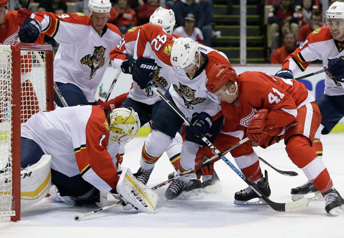 Florida Panthers center Quinton Howden (42) and Detroit Red Wings center Luke Glendening (41) look for control of the puck in front of goalie Roberto Luongo during the second period of an NHL hockey game, Sunday, Nov. 29, 2015, in Detroit. (AP Photo/Carlos Osorio) ORG XMIT: MICO105