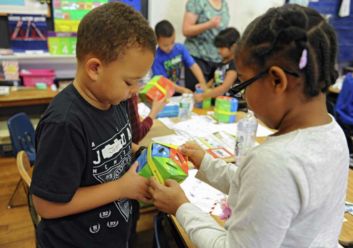 Jalen Lewis, 7, holds his Moonjar as Ayana Snipes, 7, helps put a rubber band around it during a 'Money Math: Saving, Spending & Sharing' financial literacy program being taught to second grade students at the Central Park International Magnet School on Friday, Nov. 20, 2015 in Schenectady, N.Y. The Moonjar is supposed to teach the children the concept of spending, sharing and saving money. (Lori Van Buren / Times Union)