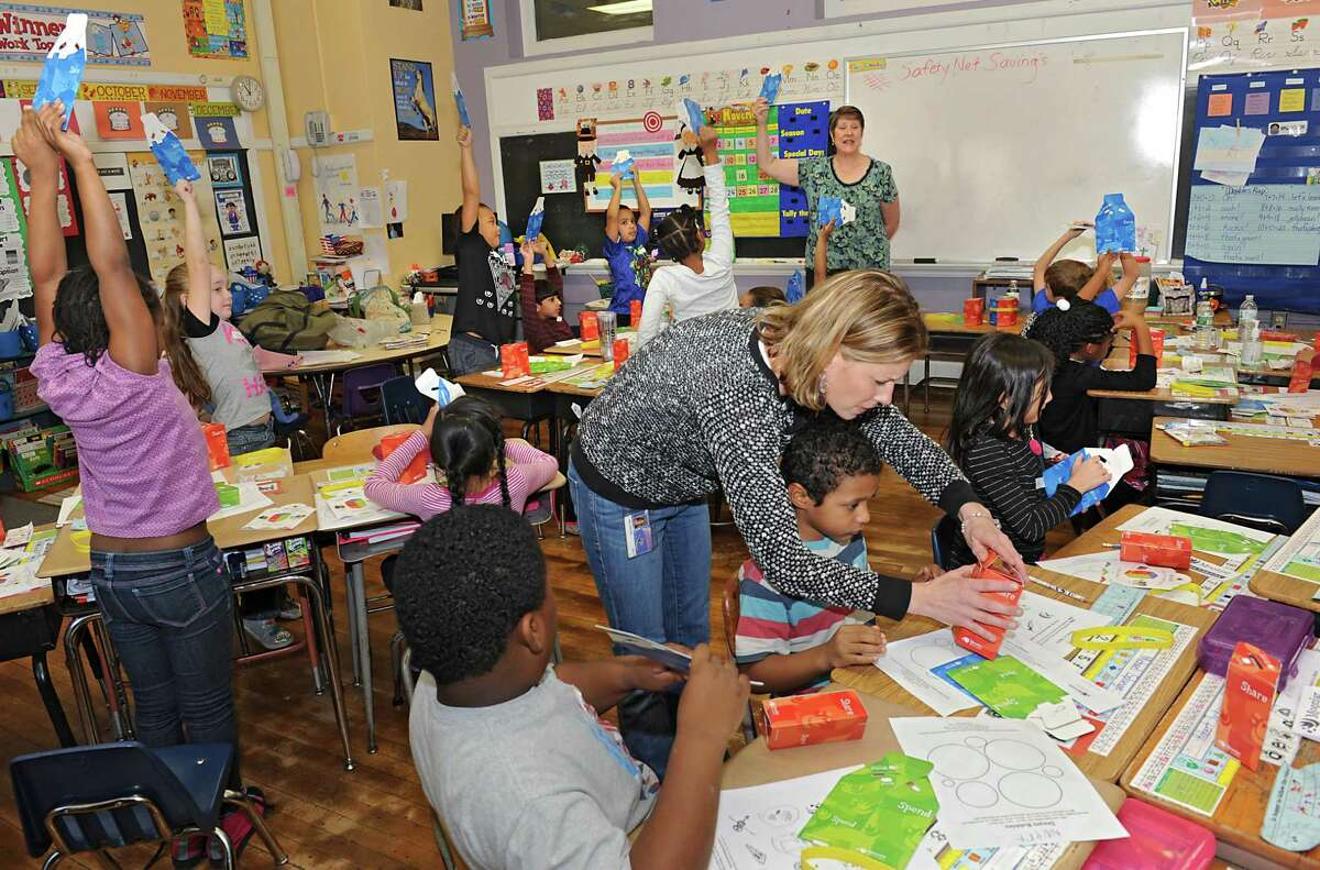 Elizabeth Lafergola, Money Math Teacher, Scotia-Glenville Children's Museum, background, speaks during a 'Money Math: Saving, Spending & Sharing' financial literacy program being taught to second grade students at the Central Park International Magnet School on Friday, Nov. 20, 2015 in Schenectady, N.Y. Amy Goyette, center, goes around and helps her second graders assemble their Moonjars which are supposed to teach the children the concept of spending, sharing and saving money. (Lori Van Buren / Times Union)