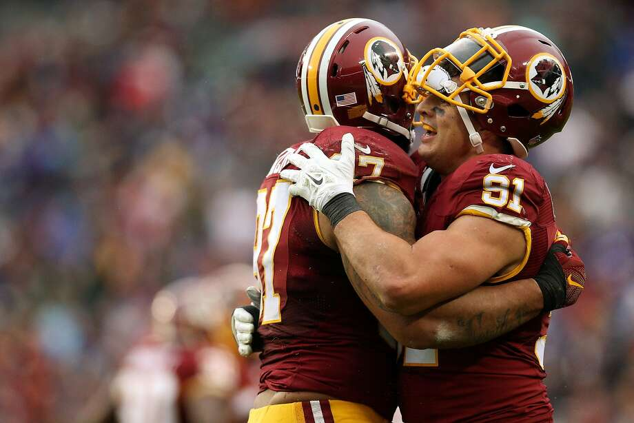 Washington's Jason Hatcher (left) and Ryan Kerrigan celebrate after a play. Photo: Patrick Smith, Getty Images