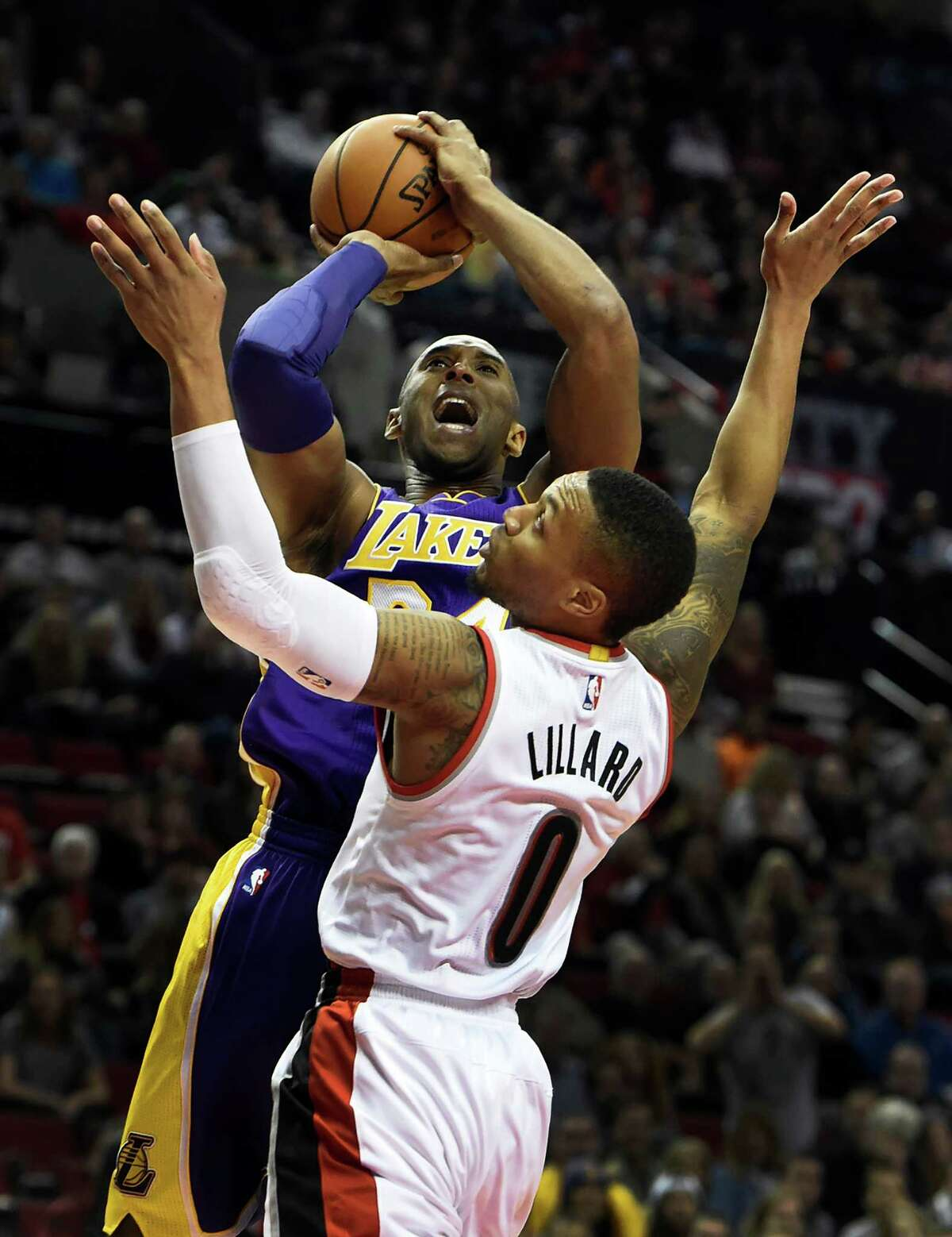 Los Angeles Lakers forward Kobe Bryant (24) shoots the ball over Portland Trail Blazers guard Damian Lillard (0) during the first half of an NBA basketball game on Saturday, Nov. 28, 2015, in Portland, Ore. (AP Photo/Steve Dykes)