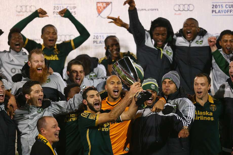 Diego Valeri of Portland raises the MLS Western Conference trophy amid joyful teammates. Photo: Ronald Martinez, Getty Images