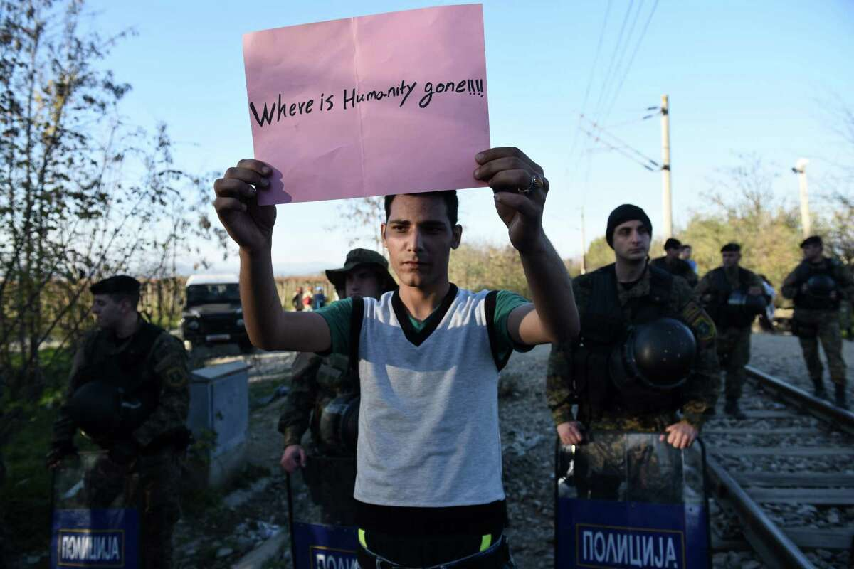 A migrant holds a sign reading ''Where is humanity gone'' at no man's land, as Macedonian policemen guard the borders of their country near Idomeni village, northern Greece on Thursday, Nov. 19, 2015. The United Nations refugee agency says Macedonia has begun allowing only people from Syria, Iraq and Afghanistan to cross its southern border from Greece, while Greek authorities say migrants of other nationalities are gathering on the Greek side of the border and blocking the crossing completely. (AP Photo/Giannis Papanikos) ORG XMIT: XTS107