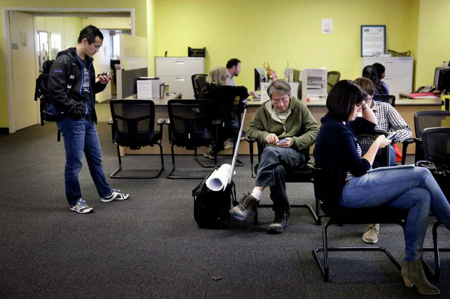 David Wang (l to r); Peter Fan, Anna Putnam and Daniel Gorham (partially seen behind Putnam) check their phones as they wait to apply for permits on the fifth floor at the Department of Building Inspection on Wednesday, November 18,  2015 in San Francisco, Calif. Photo: Lea Suzuki / The Chronicle / ONLINE_YES