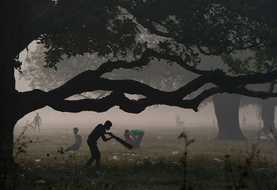 An Indian youth plays cricket in the Maidan area of Kolkata on November 29, 2015.  Photo: Dibyangshu Sarkar, AFP / Getty Images