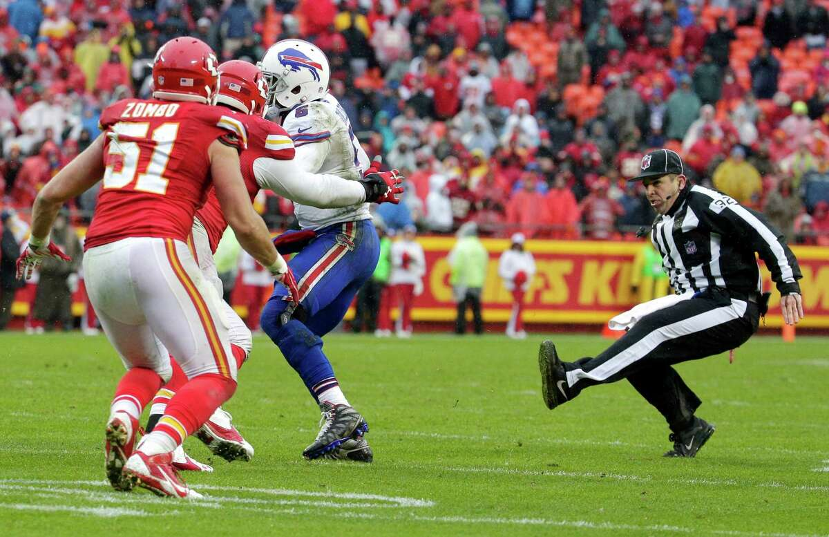 Umpire Bryan Neale, right, slips and falls while officiating the second half of an NFL football game between the Buffalo Bills and the Kansas City Chiefs in Kansas City, Mo., Sunday, Nov. 29, 2015. (AP Photo/Charlie Riedel) ORG XMIT: MONH1