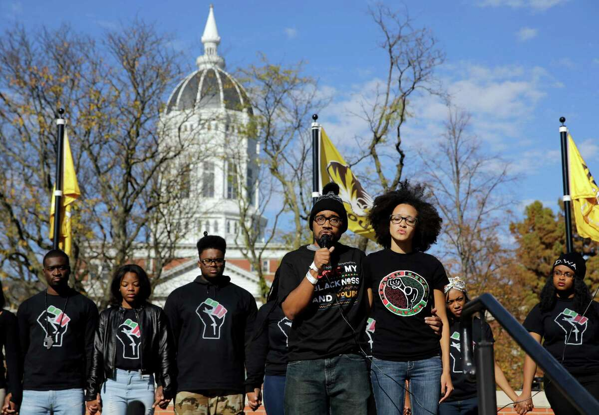 FILE - In this Monday, Nov. 9, 2015 file photo, Jonathan Butler, front left, addresses a crowd following the announcement that University of Missouri System President Tim Wolfe would resign, at the university in Columbia, Mo. Officials were slow to handle racial incidents at the University of Missouri, and that contributed to protests, a student hunger strike, a threatened boycott by the football team and ultimately, the resignations of two administrators. (AP Photo/Jeff Roberson, File) ORG XMIT: WX102