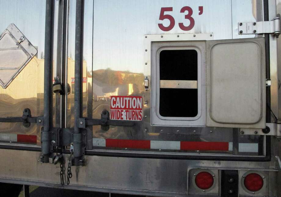 """In this Nov. 3, 2015 photo, a small door sits open on the back of a tractor-trailer parked at a truck stop in Willington, Conn. Investigators said cargo thieves can use small doors like this one to check inside truck trailers for valuable items. Investigators at The Travelers Cos., work to prevent cargo theft, including deploying a """"sting trailer"""" packed with hidden surveillance equipment. Cargo theft has become a huge problem that the FBI says causes $15 billion to $30 billion in losses each year in the U.S. (AP Photo/Dave Collins) ORG XMIT: RPDC204 Photo: Dave Collins / AP"""