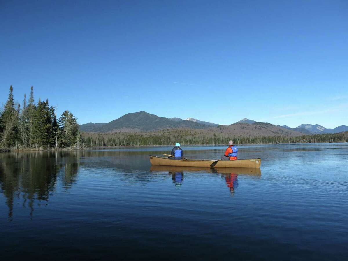 In this photo taken on Tuesday, Nov. 17, 2015, Connie Prickett, right, of The Nature Conservancy, takes a guest on a canoe tour of Boreas Pond in North Hudson, N.Y. Gov. Andrew Cuomo has committed to purchasing the 22,000-acre Boreas Pond tract from The Nature Conservancy by the end of March, completing the acquisition of 69,000 acres of former Finch, Pruyn timber company lands to expand the state?'s constitutionally protected Forest Preserve. (AP Photo/Mary Esch) ORG XMIT: RPME202